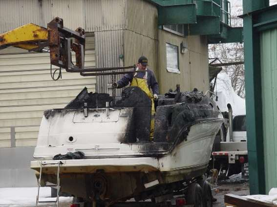 Man recycling a boat at a salvage yard